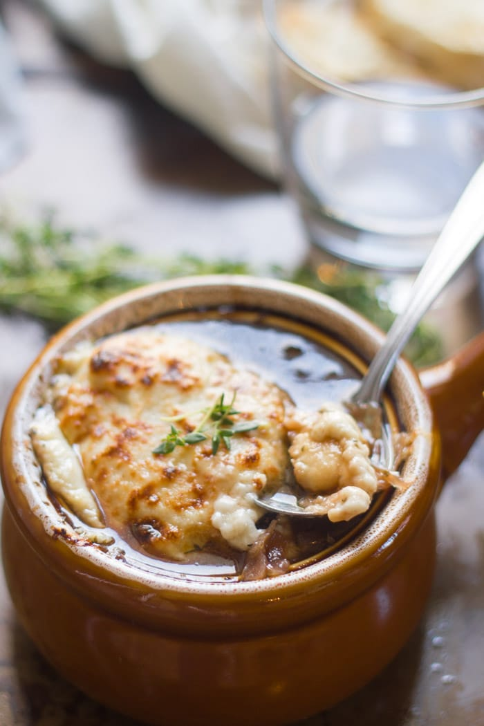 Spoon Digging into a Crock of Vegan French Onion Soup