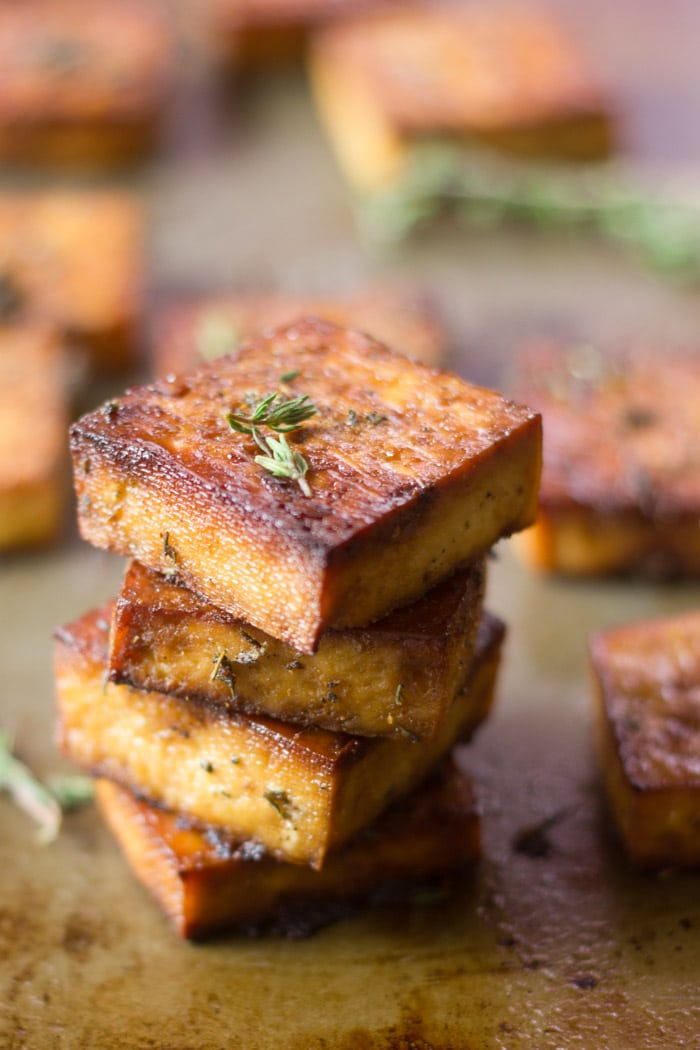 A Stack of Baked Tofu Squares with Fresh Herbs on Top