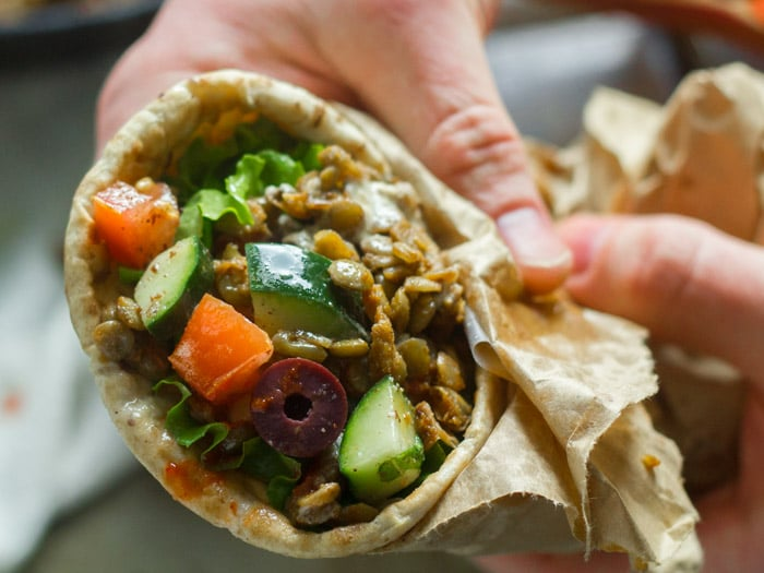 Pair of Hands Holding a Lentil Shawarma Pita