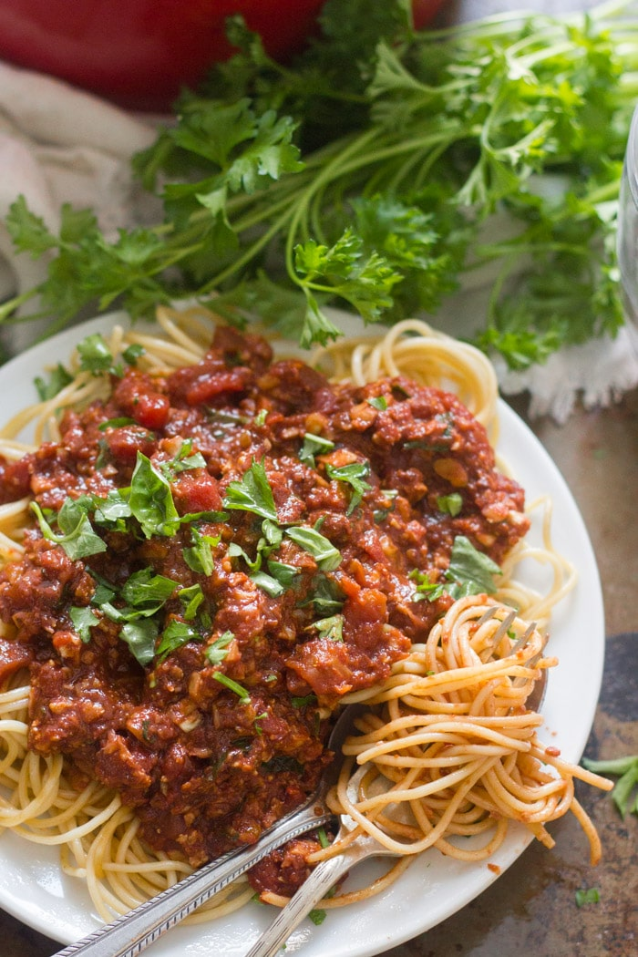 Spaghetti with Cauliflower Walnut Meat Sauce on a Plate with Fresh Parsley on Top