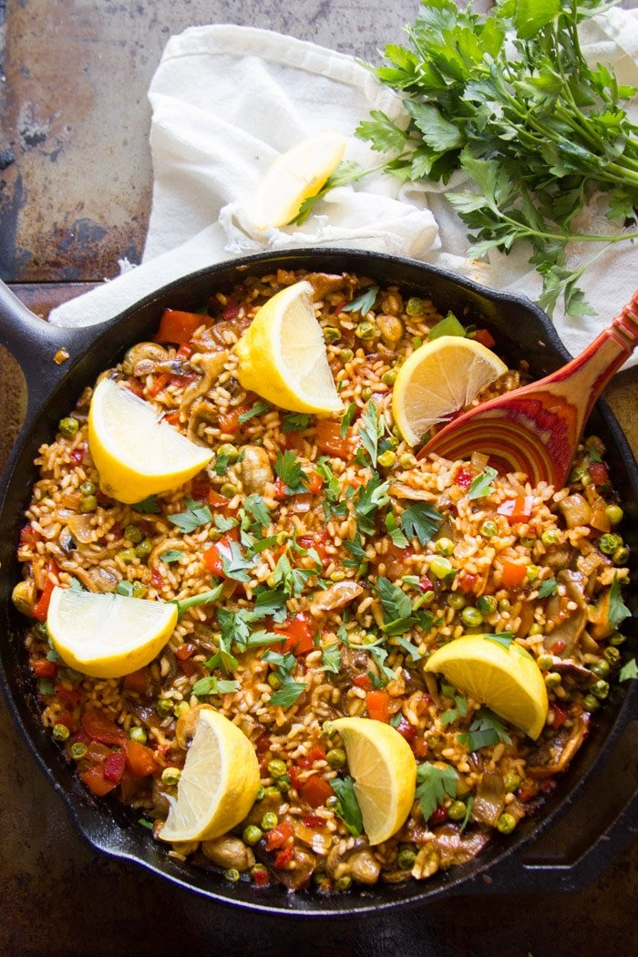 Vegan Mushroom Paella in a Skillet with Lemon Wedges on Top