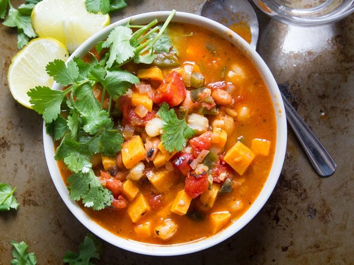 Chipotle Sweet Potato Vegan Posole in a Bowl with Spoon, Cilantro, and Lime Wedges