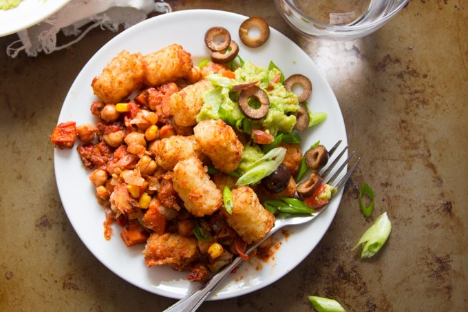 Top View of a Plate of Tex-Mex Chickpea Tater Tot Casserole with Fork and Drinking Glass