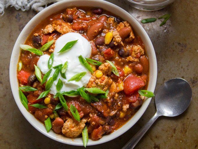 Overhead View of a Bowl of Tofu Chili Topped with Vegan Sour Cream and Scallions