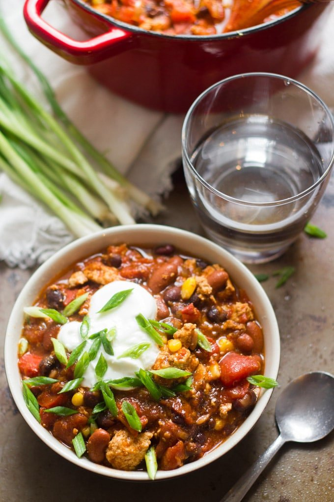 A Bowl of Tofu Chili with a Pot, Drinking Glass and Scallions in the Background