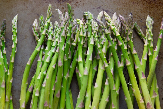 A Bunch of Asparagus Spears Arranged on a Baking Sheet