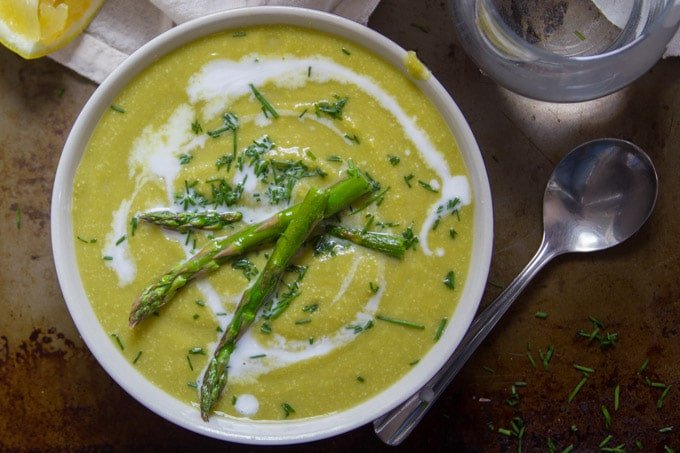 Top View of a Bowl of Vegan Cream of Asparagus Soup with Spoon and Drinking Glass