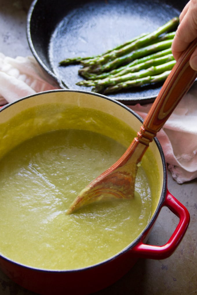 A Pot of Vegan Cream of Asparagus Soup with a Skillet of Asparagus Spears in the Background