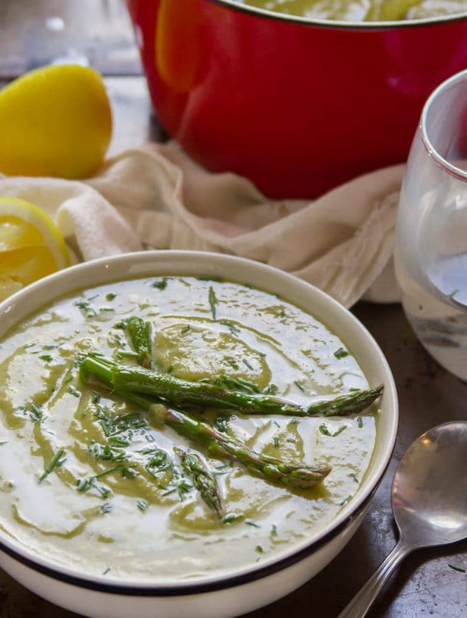 A Bowl of Vegan Cream of Asparagus Soup with a Red Pot and Lemon Wedges in the Background