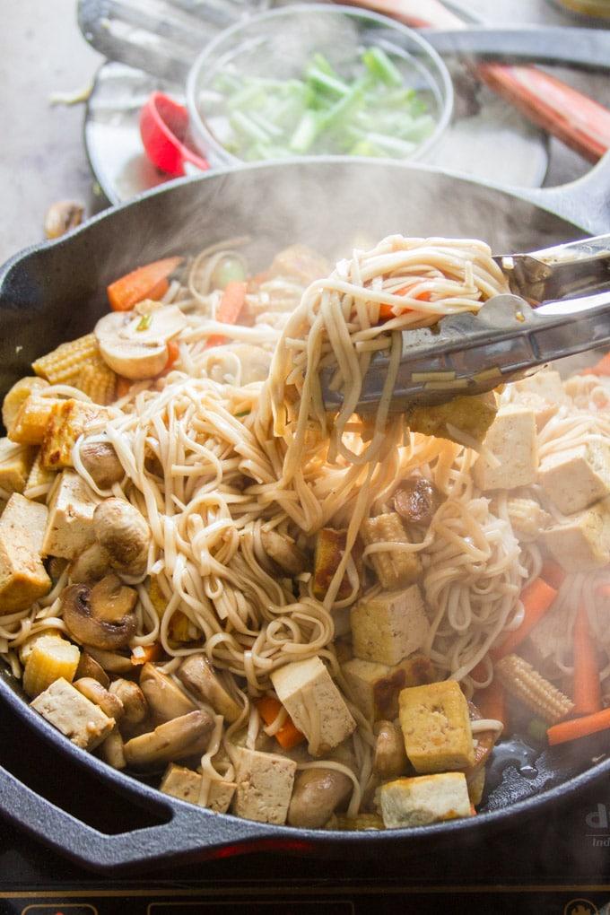 Tongs Tossing Steaming Vegan Vegetable Lo Mein in a Skillet
