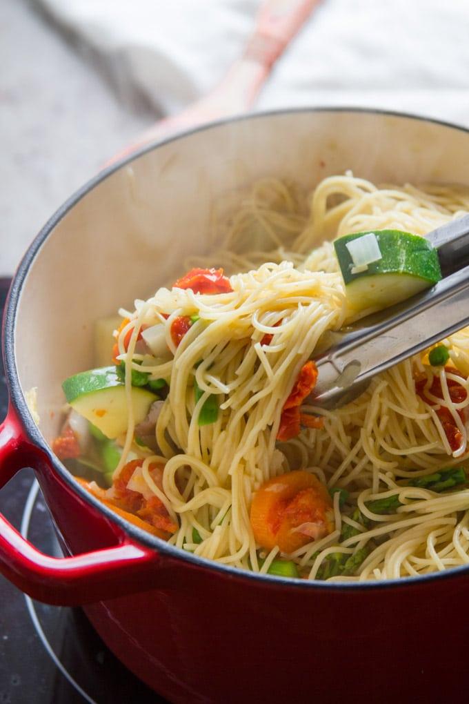 Tongs Tossing Vegan Pasta Primavera in a Pot