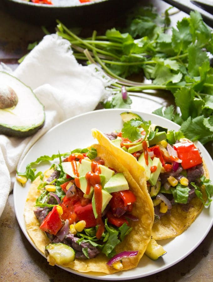 Roasted Veggie Tacos with Creamy Whipped Black Beans with Avocado and a Bunch of Cilantro in the Background