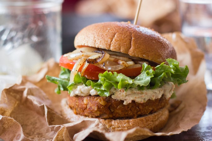 Chickpea Chorizo Burger Topped With Green Olive Cashew Cheese, Lettuce and Fried Onion