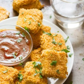 Crispy Baked Tofu Nuggets on a Plate with Dipping Sauce and Water Glass in the Background