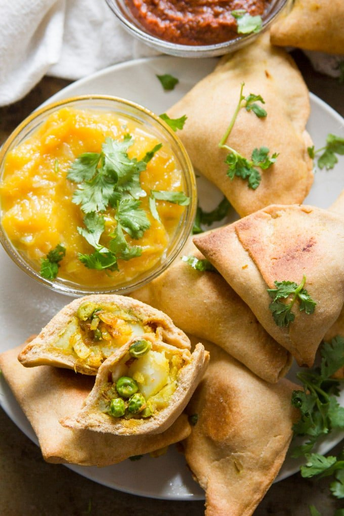 Overhead View of a Plate of Baked Vegan Samosas with a Dish of Mango Chutney