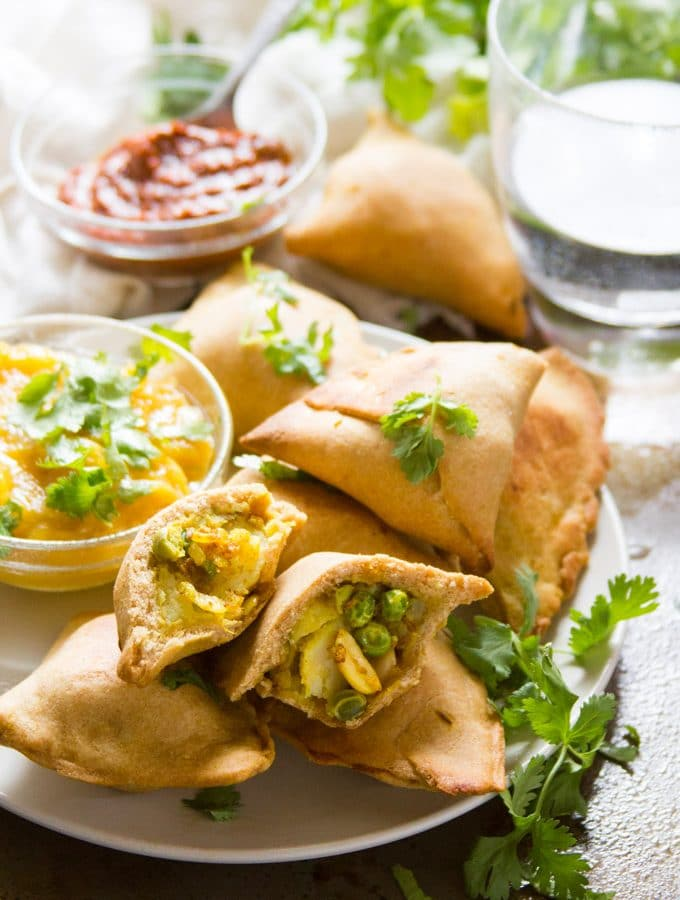 Plate of Baked Vegan Samosas with Dishes of Chutney and Water Glass in the Background