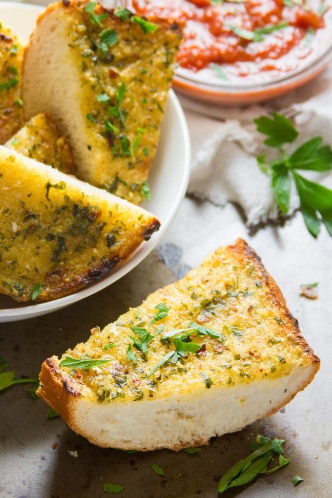 Bowl of Roasted Garlic Vegan Garlic Bread with One Slice Sitting in the Foreground