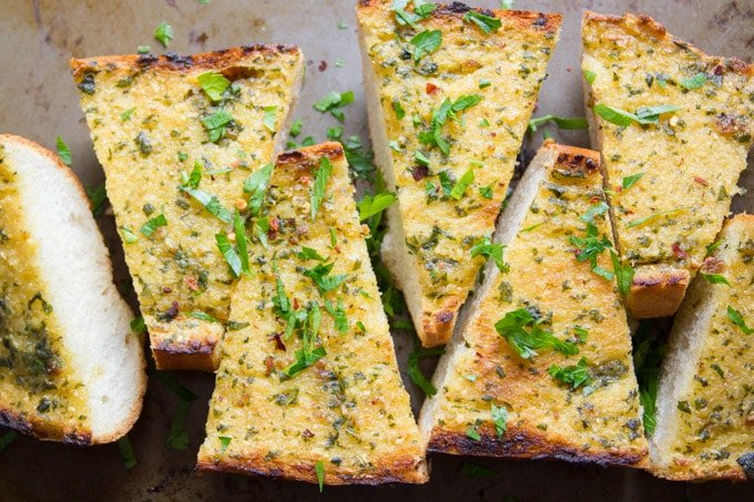 Slices of Roasted Garlic Vegan Garlic Bread Arranged on a Baking Sheet