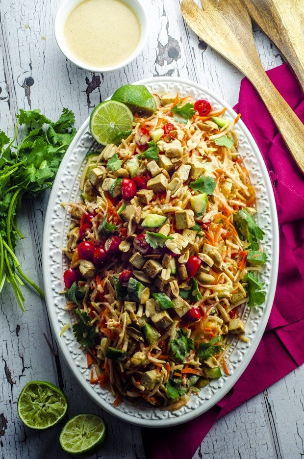 Thai Green Papaya Salad with Tofu on a Platter with Dressing, Cilantro, Lime Halves and Wooden Serving Forks