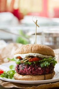 Close Up of a Beet Burger on a Plate Topped with Arugula, Tomatoes, and Cashew Cheese