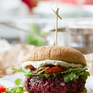Balsamic Beet Burger on a Plate with Dishes and Greens in the Background
