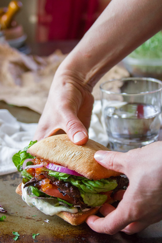Pair of Hands Grabbing a Plant-Based BLT Sandwich