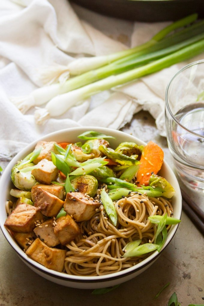 Bowl of Sesame Soba Noodles and Veggies with Scallions and Water Glass in the Background