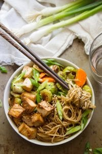 Bowl of Sesame Noodles with Roasted Veggies with a Clump of Noodles Wrapped Around a Pair of Chopsticks