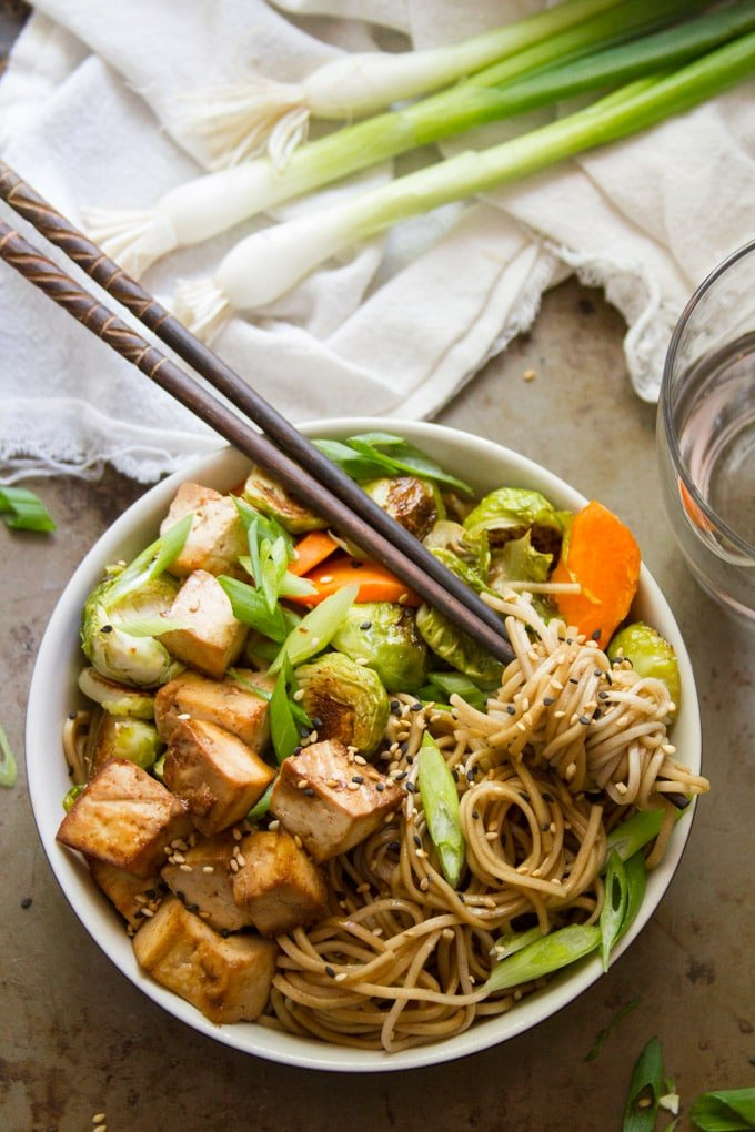 Bowl of Sesame Soba Noodles with Veggies and Baked Tofu with a Bunch of Noodles Wrapped Around Chopsticks
