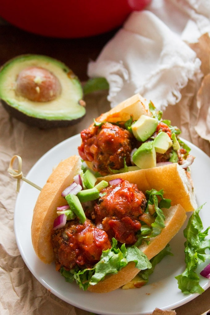 Vegan Mexican Meatball Sub on a Plate with Napkin and Avocado Half in the Background