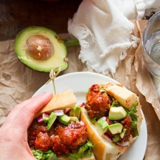 Hand Grabbing Half of a Vegan Mexican Meatball Sub From a Plate