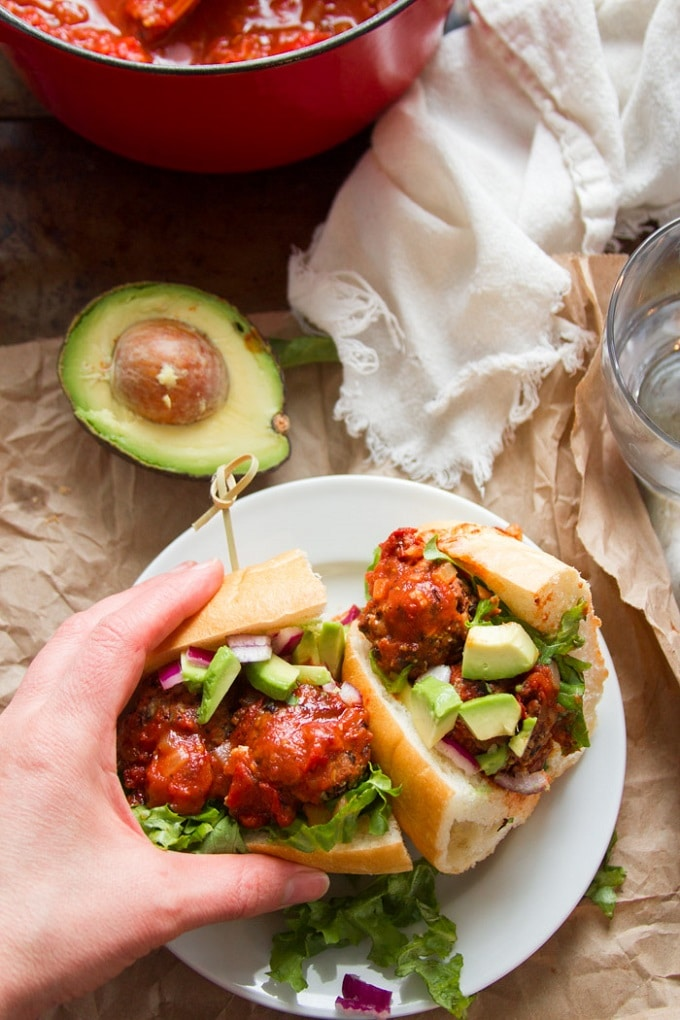 Hand Grabbing a Half of A Vegan Mexican Meatball Sub on a Plate