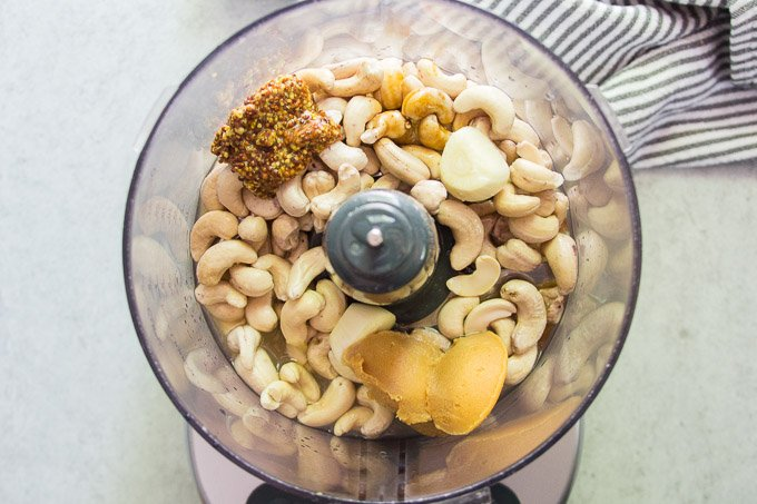 Food Processor Bowl Filled with Ingredients for Making Vegan Caesar Dressing