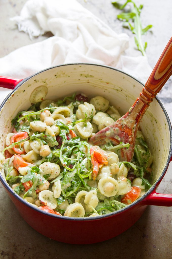 Pot of Creamy Vegan Pesto Pasta with a Large Red Spoon