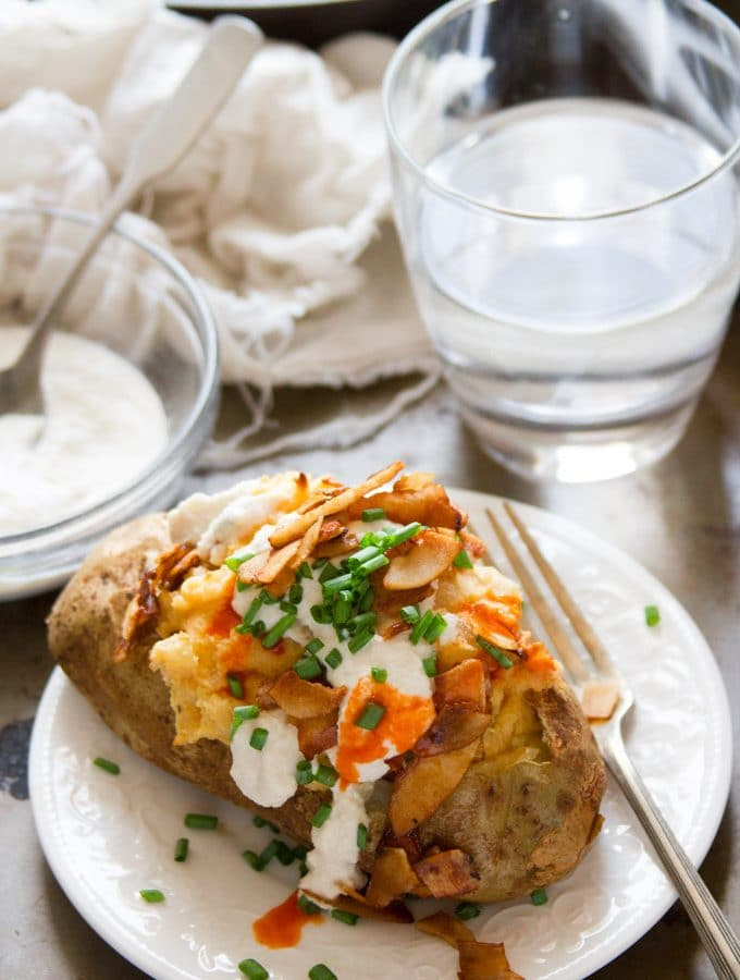 Vegan Twice Baked Potato on a Plate with Fork and Drinking Glass in the Background