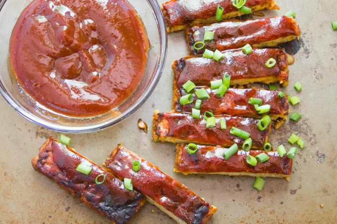 Overhead View of a Dish of Barbecue Sauce and Tempeh Vegan Ribs Topped With Scallions
