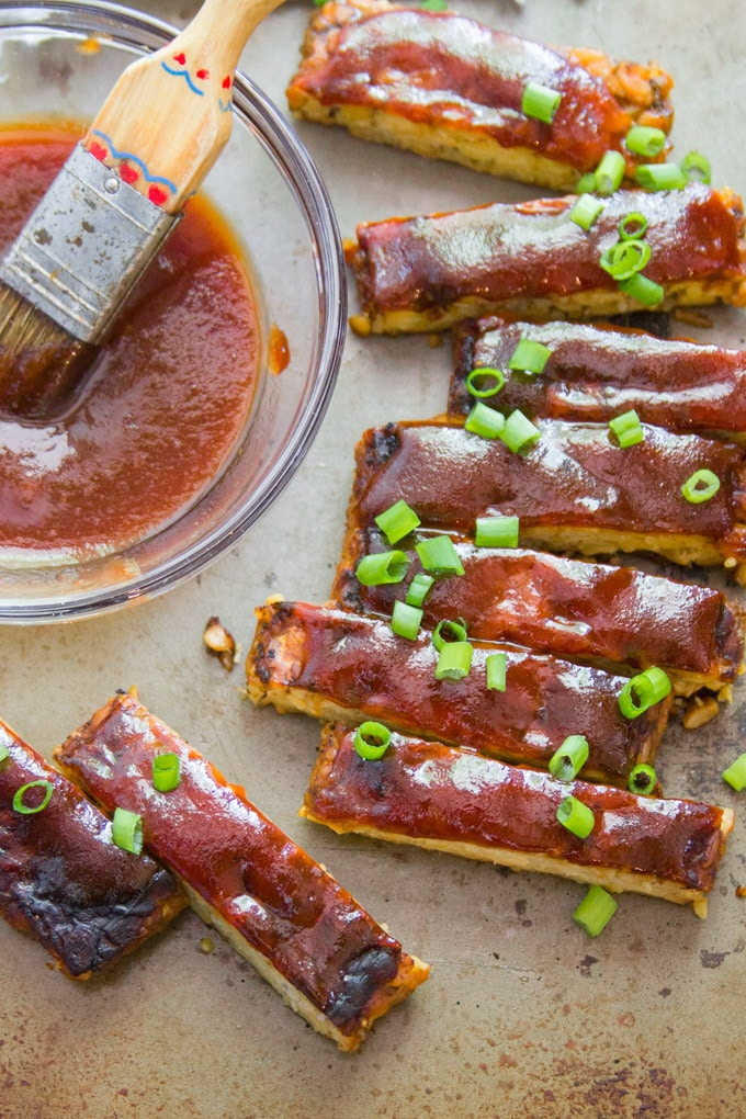 Overhead View of Tempeh Vegan Ribs Topped with Scallions and Arranged Around a Dish of Barbecue Sauce with a Basting Brush