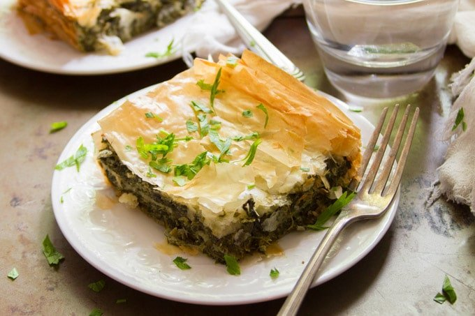 Vegan Spanakopita on a Plate with Drinking Glass in the Background