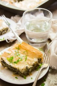 Vegan Spanakopita on a Plate with Drinking Glass, Napkin and Pan in Background