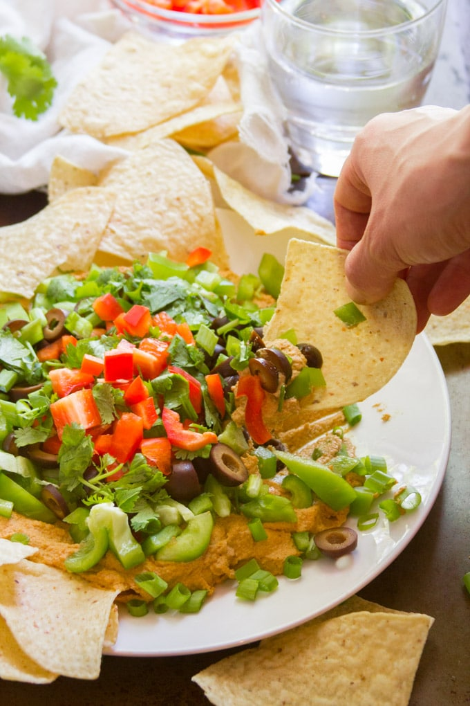 Hand Dipping a Chip into a Plate of Cheesy Vegan Taco Dip