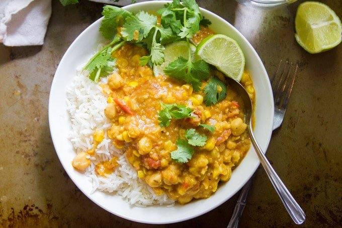 Overhead View of a Bowl of Indian-Inspired Chickpea & Summer Corn Curry Over Rice and Topped With Cilantro and Lime Slices
