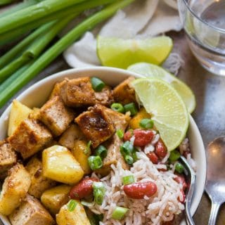 Jamaican Jerk Tofu Bowl with Fork, Lime Slices, Drinking Glass, and Scallions in the Background