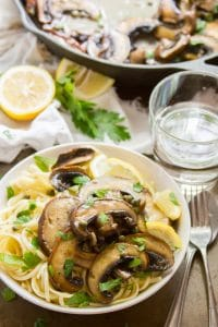 Bowl of Mushroom Scallopinin with Napkin, Drinking Glass and Skillet in the Background