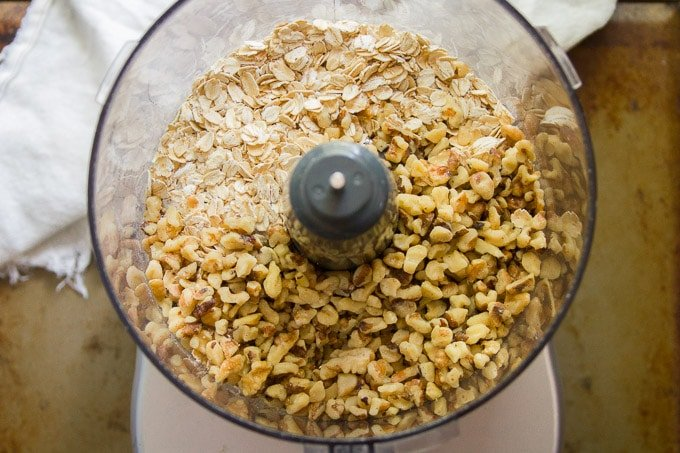 Food Processor Bowl Filled with Oats and Walnuts for Making Black Bean Walnut Burgers