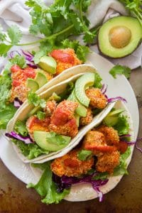 Overhead View of Three Crispy Cauliflower Tacos on a Plate with Cilantro and an Avocado Half