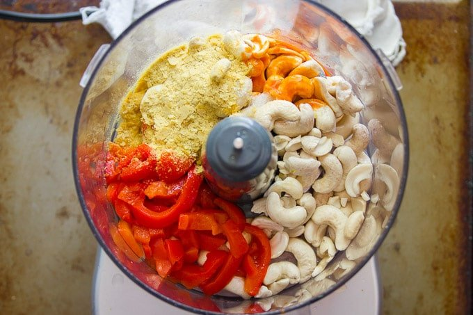 Food Processor Bowl Filled with Cashews, Pimentos, Hot Sauce and Nutritional Yeast for Making Vegan Pimento Cheese