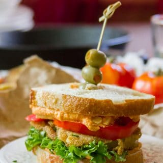 Fried Green Tomato Sandwich on a Plate with Skillet and Tomatoes in the Background