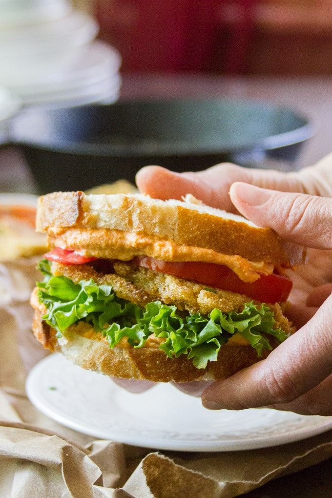 Hands Holding a Fried Green Tomato Sandwich with Pimento Cashew Cheese