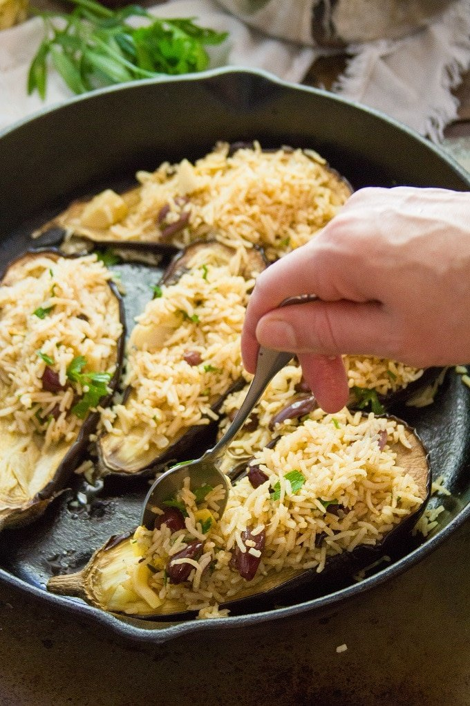 Hand Spooning Filling into Eggplant Halves to Make Mediterranean Stuffed Eggplant