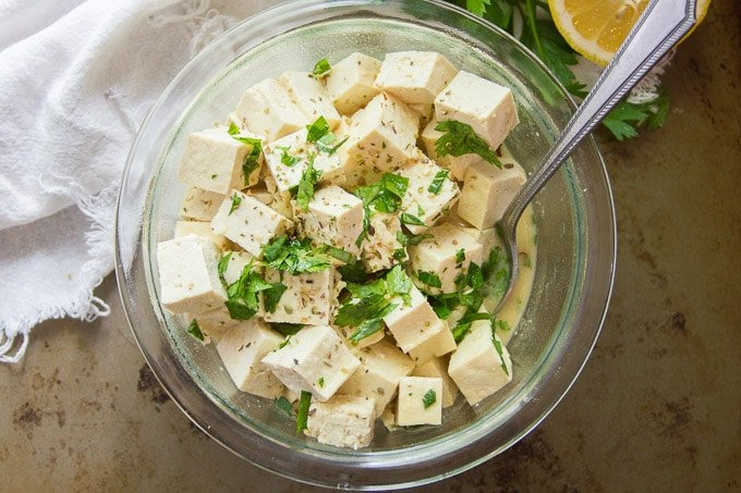 Overhead View of a Bowl of Tofu Feta Cheese with Spoon and Fresh Herbs